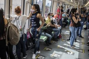 People wear face masks to prevent the spread of coronavirus as they travel on the metro amid the COVID-19 pandemic.