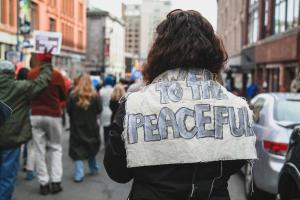 "A woman holds a cloth sign on her back that reads ""Power to the Peaceful"" at a March For Our Lives rally in Portland, Maine."
