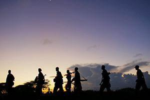 Soldiers of the Somali National Army (SNA) walk at dusk under a rising crescent moon near the outskirts of Afgooye, a town to the west of Somali capital Mogadishu.