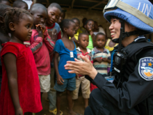 A member of the Chinese Formed Police Unit deployed with UNMIL interacts with a girl in Liberia